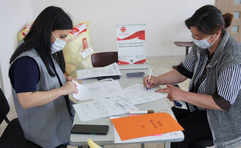 Mieszkanka ze wsi Pasar podpisuje protokół odbioru pomocy